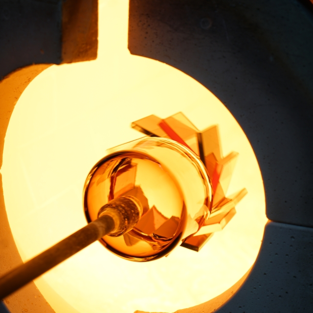 A hot glass piece, still on the end of a blowpipe, is inserted into a furnace to be reheated