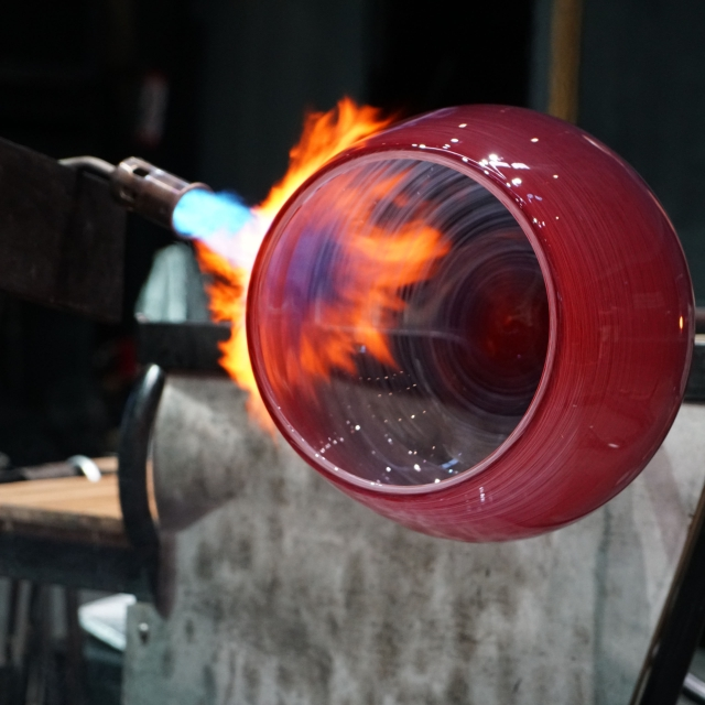 A red molten glass bowl that's engulfed in flames