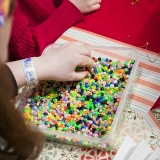 A child reaches into a box of multicolored beads
