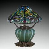 Lamp with a mosaic glass shade depicting dragonflies and flowers. The shade is held by bronze arms atop a squat base of green glass.