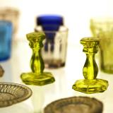 A close up of green and clear glass candlesticks that are in an exhibit case