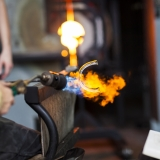 A gaffer uses a torch to heat a clear 'c' shape of molten glass