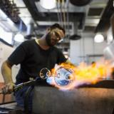 A glassblower uses a torch on a clear glass vase