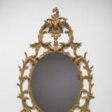 A mirror is surrounded by ornate gold filigree