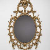 Oval mirror set in a elaborate golden wood frame
