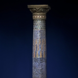 A large cylindrical column decorated with gold, blue, turquoise, and purple glass mosaic tiles arranged to resemble tassels