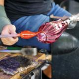 A glassblower guides a punty with molten glass to a purple glass goblet