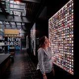 A visitor looks at a wall of small photo negatives while in an open-air room with black walls and floor tiles
