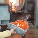 A glassblower sculpts a sphere of orange molten glass with a stack of newspapers