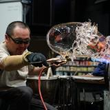 Glass artist Masahiro Sasaki uses a torch on an abstract piece of clear blown glass with tendrils wrapping around it