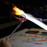 A glassworker uses a flame to heat up and twist a rod of clear glass
