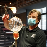 A gaffer guides a metal pole with a blob of molten glass to a blown glass sphere on a blowpipe