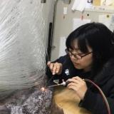 Artist Yukiko Sugano uses a long tool to melt glass onto a clear glass sculpture of tubes of glass