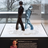 Two glass human figures in brown and blue are in a glass exhibit case