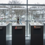 Four exhibit cases hold glass sculptures