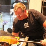 George Kennard shapes hot glass at the bench during a live demo.