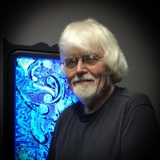Eric Hilton smiles in front of a blue and white swirled piece of glass