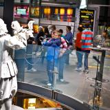 A child and an adult smile use using two magnifying glasses to look at two white sculptures of glassblowers