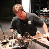 Jeff Mack creates a platter in clear glass during a demo at the bench.