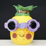 A glass pineapple sculpture with purple sunglasses