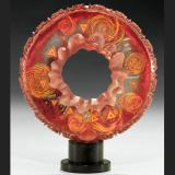 A donut-shaped red, pink, and orange glass sculpture with circles and triangles patterns