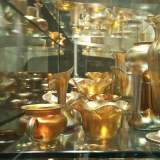 An exhibit case of gold vases that vary in size